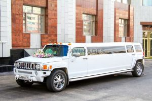 White limousine Hummer H3 on a city street.