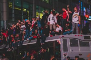 people standing around and on top of a party bus