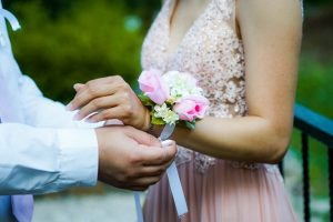 a closeup of a guy put a corsage on his prom date
