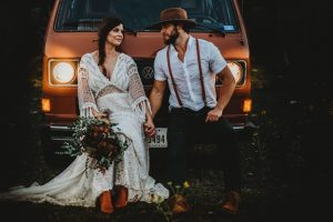 Couple photographed on their wedding in front of a car
